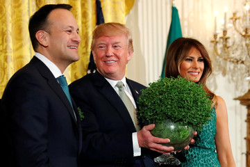 U.S. President Donald Trump, flanked by first lady Melania Trump, receives a bowl of shamrocks from Ireland's Prime Minister, Taoiseach Leo Varadkar during a St. Patrick's Day reception at the White House