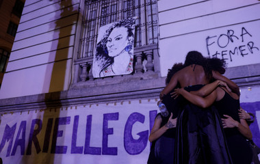 Demonstrators react next to a draw representing the Rio de Janeiro city councilor Marielle Franco who was shot dead in Rio de Janeiro, during a rally against her death Brazil