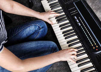 Practicing electronic keyboard on the floor