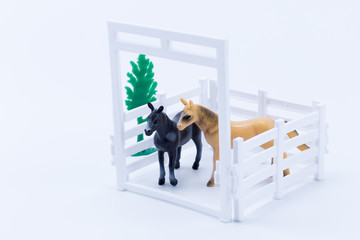 Two toy horses black and brown in a white pen with small green tree in white background