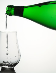 Mineral water pour from green bottle into clear glass