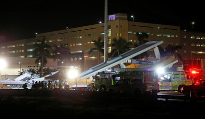 First responders are shown as rescue efforts continue after a pedestrian bridge collapsed at Florida International University in Miami