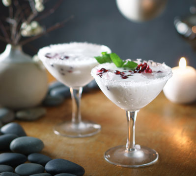 White holiday mimosa in martini glasses with pomegranate and mint garnish