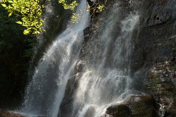Waterfall over the dark rock in the forest