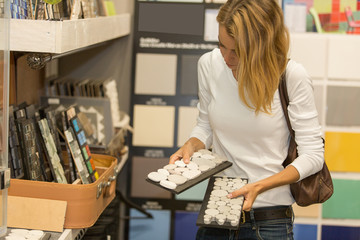 woman choosing hardware in store for new house