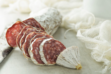 Sliced gourmet salami with white casing