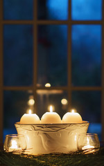 Three candles burning by window with evening blue sky outside