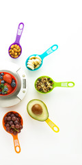 Food scale surrounded by nuts and fruits in colorful measuring cups