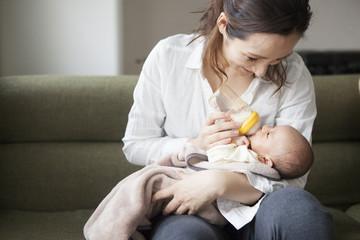 ソファに座って子供にミルクを飲ませる母親