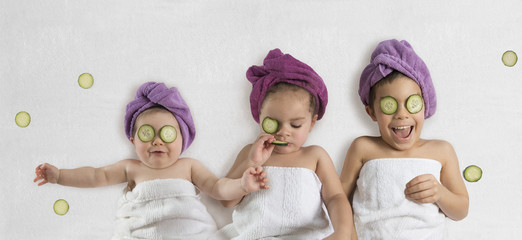 Cute, funny kids in white towels and terry cloth bath turbans with cucumber face treatments