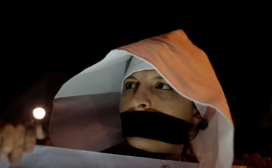An activist dressed in a costume from The Handmaid's Tale takes part in a protest and vigil against femicide in San Jose