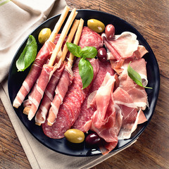 Plate with prosciutto, salami, bread sticks and olives.