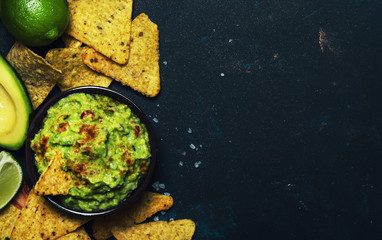 Mexican food, guacamole sauce with avocado, onion, garlic and chili, black background, top view