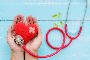 World health day, Healthcare and medical concept. Woman hand holding red heart with Stethoscope,  yellow Pill on Pastel white and blue wooden table background texture.