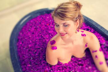Stress free woman relaxing in romantic flower bath