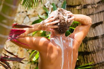 Man washing hair outdoors