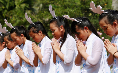 Schoolgirls perform during the 50th anniversary of the My Lai massacre in My Lai village
