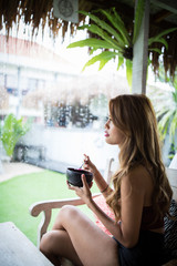 Young girl having breakfast while it rains at a cafe.