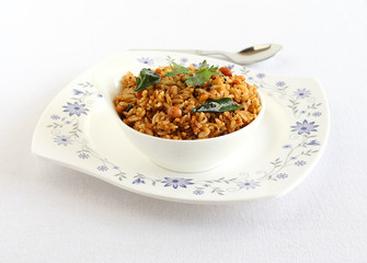 Puliyogare, south Indian traditional and popular vegetarian rice dish, in a bowl on a plate.