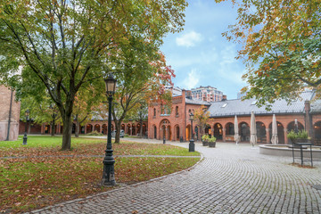 a walking pave behind Oslo Church through foliage trees and red brick building undr blue sky