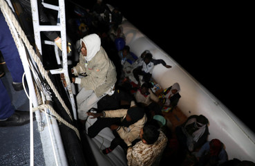 Migrants in a dinghy are rescued by Libyan coast guards in the Mediterranean Sea
