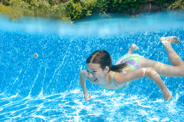 Child swims in swimming pool underwater, happy active teenager girl dives and has fun under water, kid fitness and sport on family vacation on resort