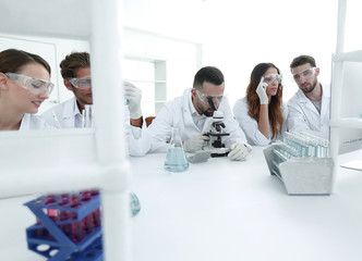 background image is a group of scientists working in the laboratory.