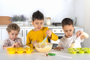 The little girl and two boys cook cake in kitchen of the house.