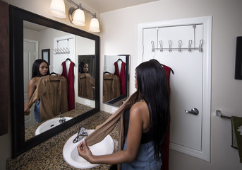 Black female deciding between dresses and thinking about choosing a stylish fashion to wear.  She is getting ready trying on clothing from shopping.  The woman is looking at a mirror in the bathroom.