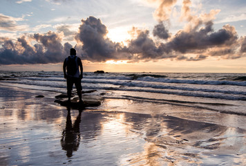 Rear view of a Man with beautiful reflection during sunset at Kudat, Sabah Malaysia.