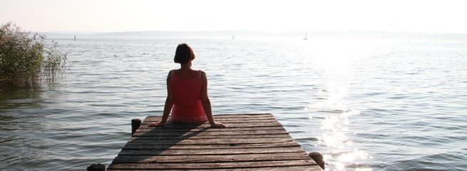 Frau sitzt auf einem Steg Panorama