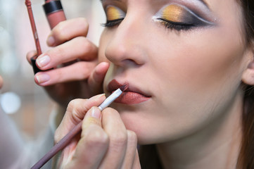 professional makeup artist applying makeup for young woman in studio