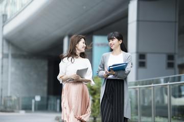女性社員たちが資料を持ちながら外を歩いている