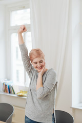 Elated attractive woman gesturing with her fist