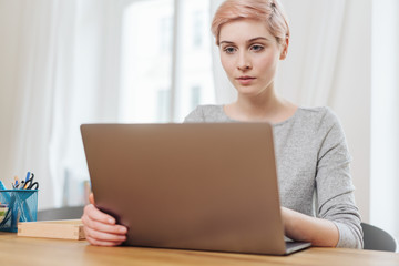 Serious young woman working on a laptop