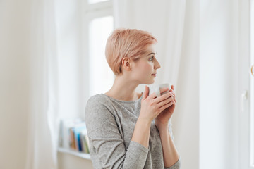 Thoughtful young woman drinking a mug of coffee