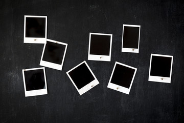 Blank grungy photo frames attached to a metal blackboard with magnets