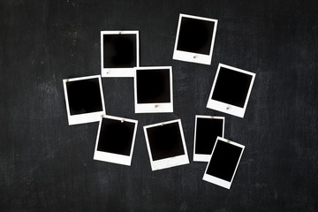 Blank retro photo frames attached to a metal blackboard with magnets