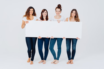 Four attractive barefoot women holding a sign