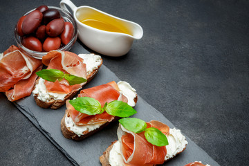 italian food with olives and prosciutto bruschettas on stone board