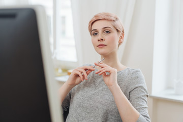 Thoughtful young woman reading on a computer