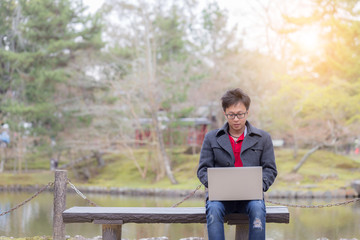 Happy Business Asian Man working with labtop outdoor in park