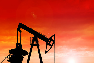 Silhouette of oil pump at sunset.