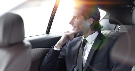 successful man sitting in the back seat of a car
