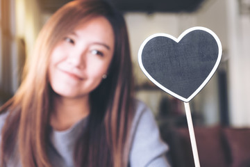 A beautiful asian woman holding a blank heart shape blackboard sign with feeling happy and in love