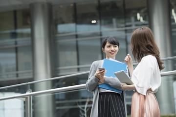 オフィスビルで会話をする女性たち