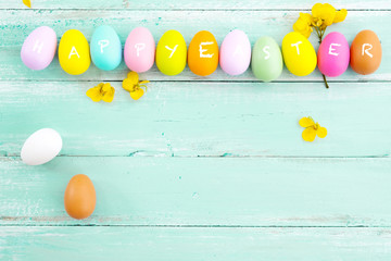 Wall Mural - Colorful Easter eggs with flower on rustic wooden planks background in blue paint. Holiday in spring season. vintage pastel color tone. top view composition.