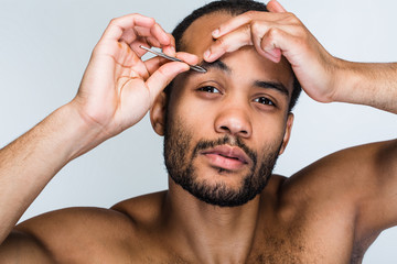 Real metrosexual. Portrait of handsome shirtless young black man looking at camera and pampering his eyebrow while standing against white background