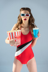 seductive girl in 3d glasses holding popcorn with drink and looking at camera isolated on grey