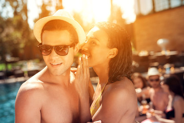 c1f7f4796ef Young black girl in swimsuit gossiping with young handsome guy in straw hat  near pool.